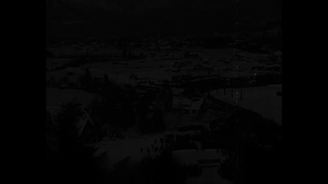 norway wins the winter olympic games / tiltdown ws snowy scene of garmischpartenkirchen with crowds at winter olympics opening ceremony / bundledup... - garmisch partenkirchen stock videos & royalty-free footage