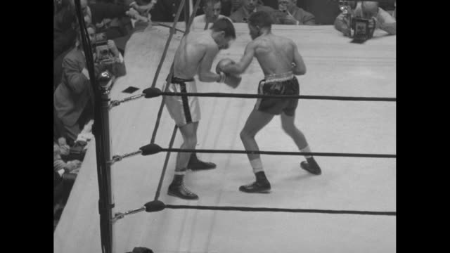 "vs. chicago golden gloves!"" superimposed over boxing match / vs billy hill punches jack corvino against ropes / spectator covers eyes with gloved... - cut video transition stock videos & royalty-free footage"