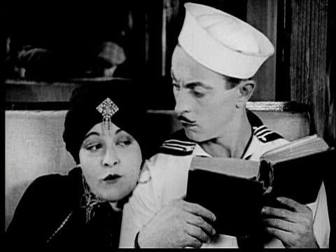 1925 B/W MONTAGE CU Title card of woman's eyes / CU Woman (Madeline Hurlock) flirting with sailor (Sidney Smith) on train / MS Sailor dropping book out window, then wind blows his hat off / WS Sailor running down aisle / Los Angeles County, California, USA