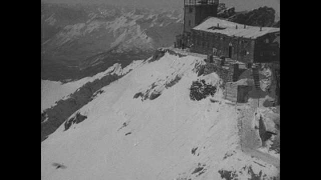 "vídeos de stock, filmes e b-roll de ""olympic fans jam towns in bavarian alps"" / residence on top of snowy mountain in bavarian alps; pan across snow-covered mountains to ski lift / from... - garmisch partenkirchen"