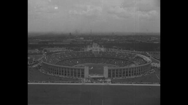 olympics come to close us big winner / title card berlin superimposed over aerial of olympiastadion berlin / high angle view of crowds milling around... - 1936 stock-videos und b-roll-filmmaterial