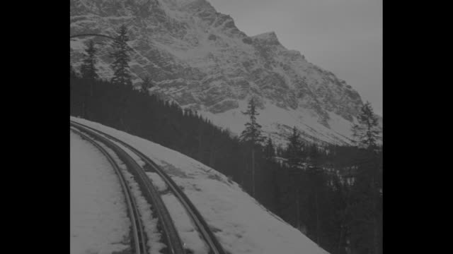 "vídeos de stock, filmes e b-roll de ""olympics draw thousands to german alps"" / train approaches, passing snow, as it moves in the bavarian alps / soldier looks out train window at... - garmisch partenkirchen"
