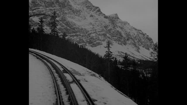 vídeos de stock, filmes e b-roll de olympics draw thousands to german alps / train approaches passing snow as it moves in the bavarian alps / cu soldier looks out train window at scenic... - montanhas wetterstein