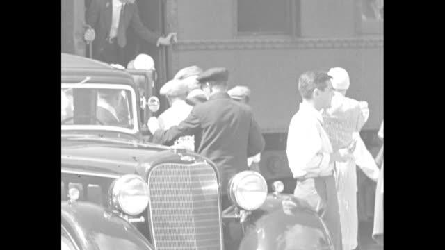 'Ormond Beach Fla John D Rockefeller Sr now 95 arrives for winter' / Rockefeller in wheelchair is slowly moved from railroad car / wearing sunglasses...