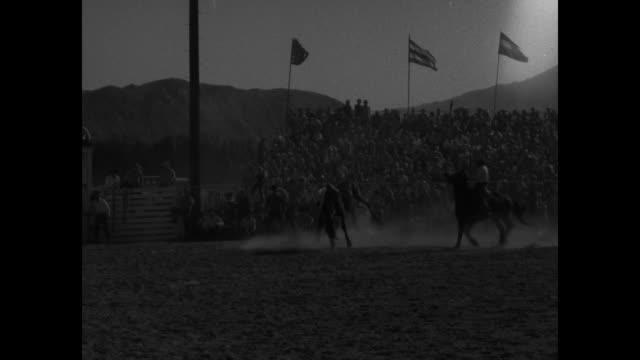palm springs rodeo superimposed over man riding bucking bronco / ws man rides bucking bronco out of gate toward camera is bucked off crowd watches... - bocksprång bildbanksvideor och videomaterial från bakom kulisserna