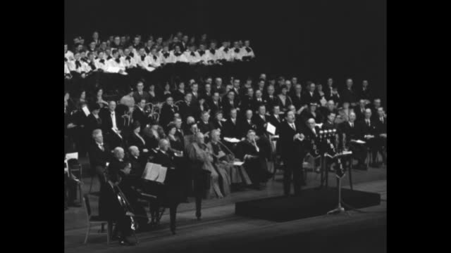 vídeos y material grabado en eventos de stock de papal count john mccormack / john mccormack standing at podium on stage in front of notables sitting behind him including new york archbishop patrick... - servicio religioso