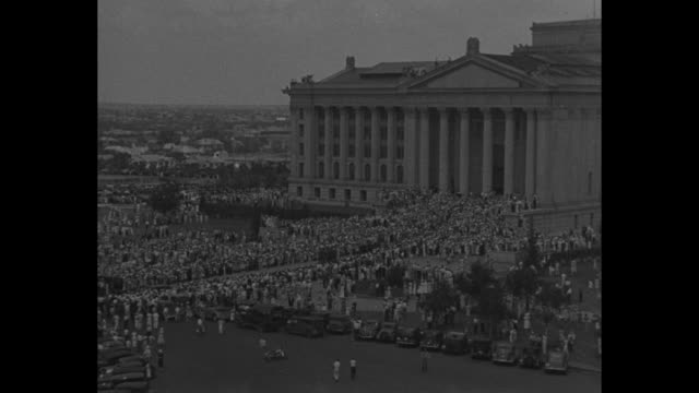 stockvideo's en b-roll-footage met paramount news special / rogers post go to rest / aerial oklahoma state capitol building with thousands of people / american flag at half mast /... - weduwe