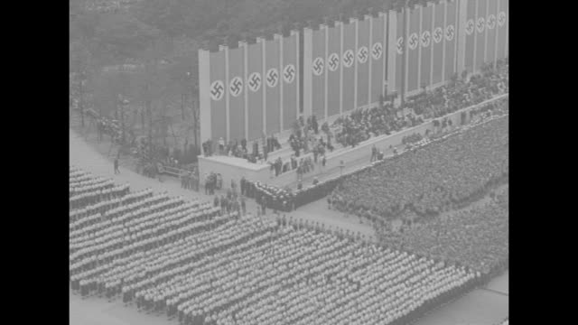 """paramount news special!"" / rotating star animation over olympic flame / title card: òfirst pictures opening of olympic games"" / dissolve to title... - nazi swastika stock videos & royalty-free footage"