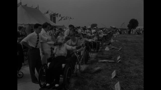 paraplegics star athletes in world meet superimposed over men moving toward camera in wheelchairs and bearing banners / ls wheelchair athletes parade... - 表す点の映像素材/bロール