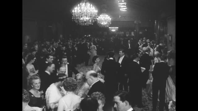 """""""pathe news"""" / title card: """"royal film performance"""" superimposed over attendees / high angle of many people in formal attire / unid couple / former... - peter ustinov stock videos & royalty-free footage"""