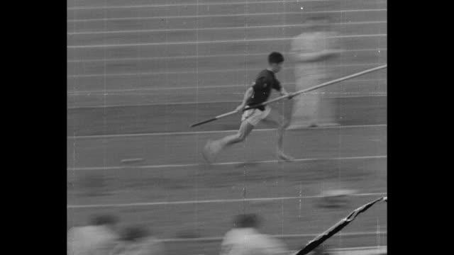 pole vault superimposed over man pole vaulting at berlin's summer olympics / japanese pole vaulter shuhei nishidia runs vaults / slomo close up... - summer olympic games stock videos and b-roll footage