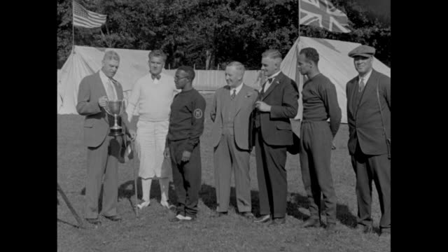 'Presenting the cup of victory' / man presents trophy to University of Michigan runner Eddie Tolan as others look on / MS Tolan with trophy saying a...