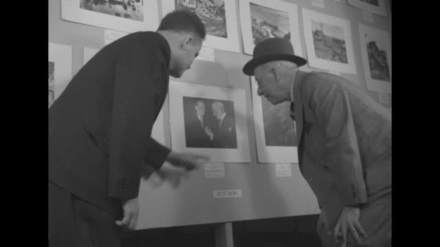 stockvideo's en b-roll-footage met press pix prizes given for best news photos / in gallery in empire state building two women and man look at photographs on wall / al smith former... - al smith