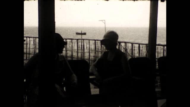 """title card """"puntarenas costa rica""""; panning view of people talking inside a building overlooking the pier, boats in the background; road leading to a... - costa rica stock videos & royalty-free footage"""
