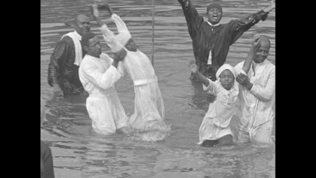 purifying the righteous / people on a riverbank look on as a preacher dunks churchgoers in water / vs after women are dipped beneath the water they... - sonntag stock-videos und b-roll-filmmaterial