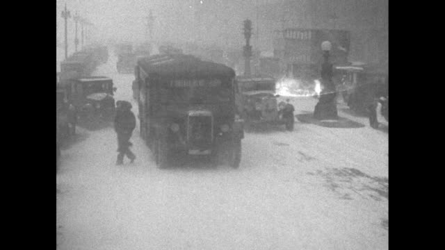 """""""raging blizzard greets spring in the midwest-whipped by fierce gale, storm turns chicago into maelsrom of snow and sleet"""" / slow-moving traffic in... - 1930~1939年点の映像素材/bロール"""