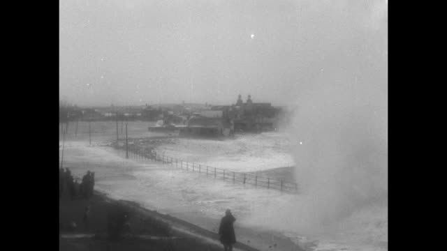 """""""raging seas smash ships and coast"""" / various shots of large waves smashing into seawall / various shots of cottages along shore being flooded and... - north america stock videos & royalty-free footage"""