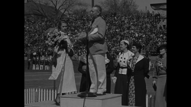 vídeos y material grabado en eventos de stock de record drake relays / vs martha stull queen of the drake relay with bouquet rides atop car she stands with man atop raised platform crowned with... - corona arreglo floral