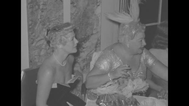 'Red Hot Sophie 50 Years in Show Business' superimposed over entertainer Sophie Tucker standing and singing with people at tables in background / WS...