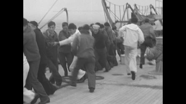 """""""rescue of man at sea!"""" / the trawler cambridge is towed by a very long rope from the coast guard cutter cayuga; men running about the cayuga's deck;... - cayuga stock videos & royalty-free footage"""