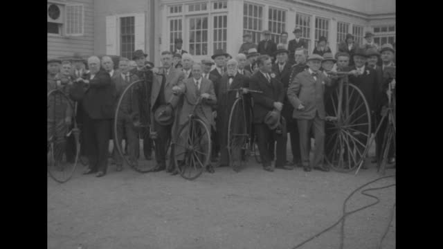 RIDING HIGH Era of 'bicycle built for two' revived by veteran wheelman / WSPAN group of men stand with their highwheel bicycles / MS men ride off on...