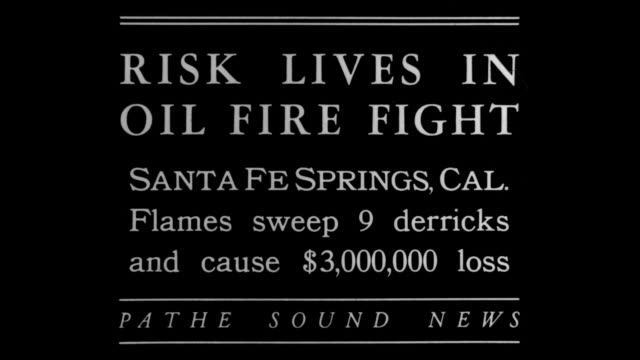 """stockvideo's en b-roll-footage met """"risk lives in oil fire fight - santa fe springs, cal - flames sweep 9 derricks and cause $3 000 loss"""" / fire burning, oil derricks in background /... - fire hose"""