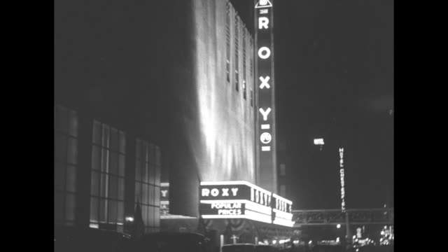 """radio city's new picture palace gives you a glimpse of theater of future"""" / vs night ext rko roxy theatre with flashing neon signs / mls low angle... - agua点の映像素材/bロール"""