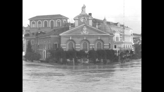 """""""rome's old man river"""" / vs tiber river flooding in rome, people watching / men on makeshift raft rescuing woman from house / two shots of men... - テベレ川点の映像素材/bロール"""