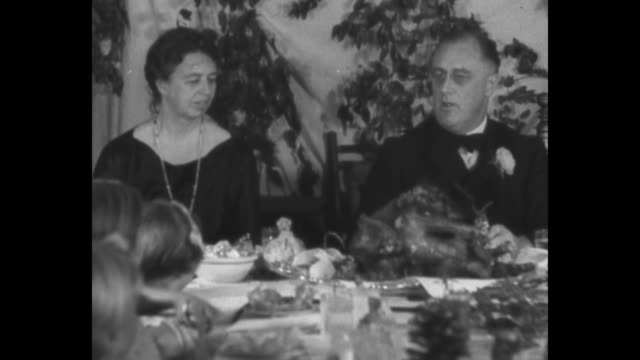 Roosevelt entertains 'Little Women' / Pres Franklin Roosevelt with first lady Eleanor Roosevelt at end of table carves turkey as children look on he...