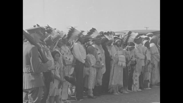 """""""roosevelt inspecting ft. peck dam"""" / crowded sidewalks at business district; some buildings with false fronts / numerous blackfoot indians wearing... - indigenous peoples of the americas stock videos & royalty-free footage"""