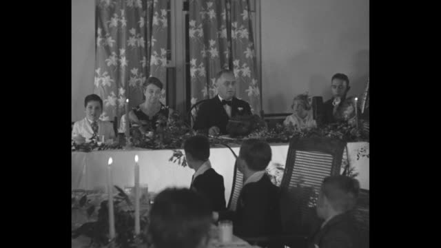 roosevelt talks turkey / pres franklin roosevelt and first lady eleanor roosevelt sitting at table with children other children at other table in... - thanksgiving politics stock videos & royalty-free footage