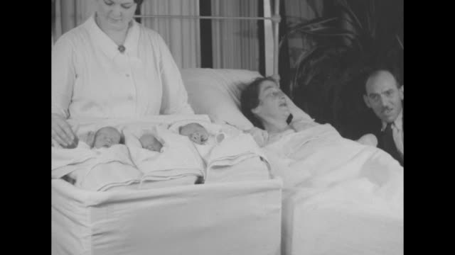 Roosevelt Trio Pittsburgh triplets just delivered by stork named for candidate / mother Anna Henry in bed husband James Henry sits bedside babies on...