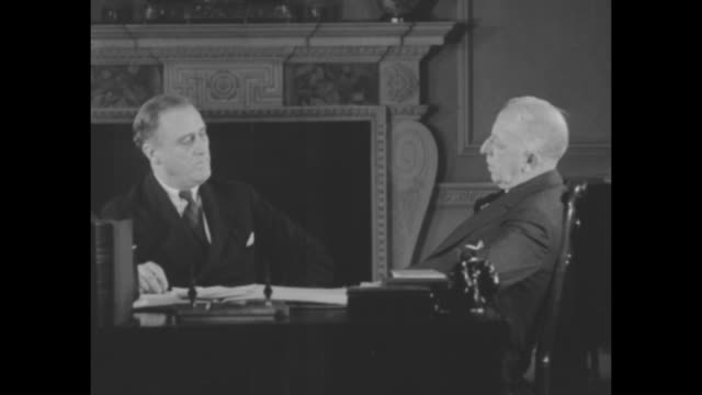 vídeos de stock e filmes b-roll de roosevelt urges a tax holidayalbany nygovernor says legistature can help business and unemployment / fdr sitting at desk speaks to man at side of... - 1931