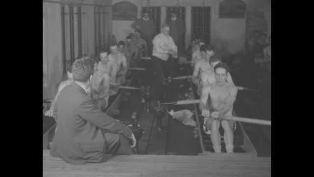rowing season nearprinceton oarsmen start indoor practice under coach sikes / rowers work out in rowing machines gordon sikes coaching back of man... - canottaggio video stock e b–roll