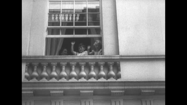 royal tots help grandma celebrate birthday superimposed on queen mother and princess ann waving from window of clarence house at crowd below / crowd... - nurse waving stock videos & royalty-free footage