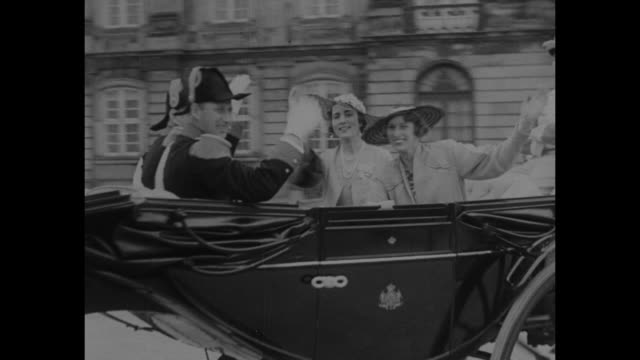 royalty holds the headline superimposed over procession of open carriages / king christian and queen alexandrine ride in open carriage in procession... - principe persona nobile video stock e b–roll
