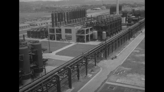 'Rubber Huge synthetic plant goal 90000 tons a yr' / two men at side of railroad tracks with large cylindrical alcohol storage tanks at left /...