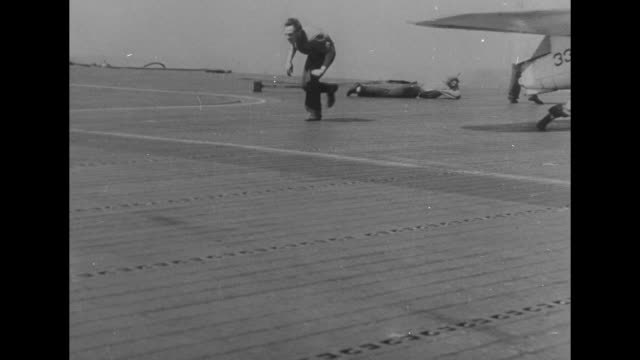 'Sea Fight US Carrier Downs Jap Torpedo Planes' / VS United States Navy carrier ship at sea / VS sailors on deck with planes some seek cover as...