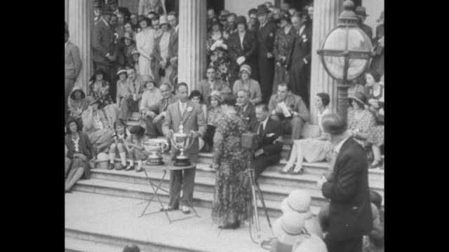 she beat 86 men for this trophy/ pilot winifred brown stands with man at table with silver trophies after winning the king's cup as numerous people... - paramount building stock videos and b-roll footage