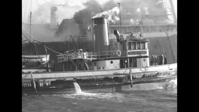 """""""ship fire - gas blaze perils ny waterfront"""" / two shots of tugboat anchored alongside freighter """"silverash"""" next to pier, smoke coming from... - anchored stock videos & royalty-free footage"""