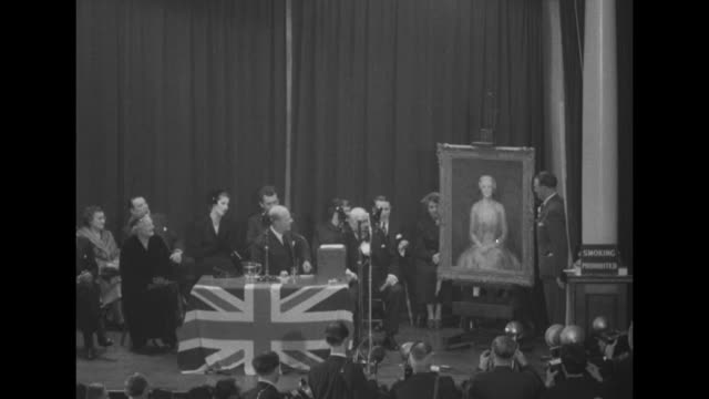 'Sir Winston Gets a Birthday Gif' superimposed over Churchill at rostrum on stage / audience of mostly women applauding / portrait of Lady Churchill...