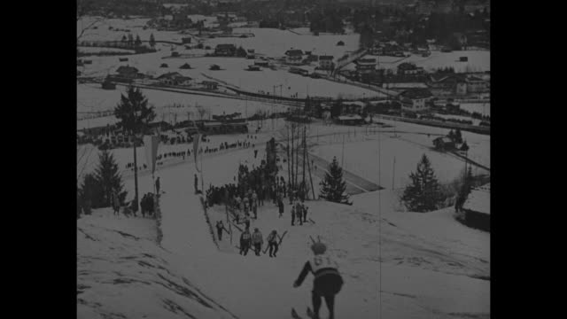 "vídeos de stock, filmes e b-roll de ""ski in german alps! garmisch, ger. - starting 1931 on the jump! snow artists show skill in exciting meet high amid picturesque peaks."" / crowd-lined... - garmisch partenkirchen"
