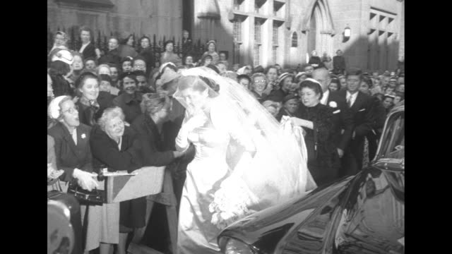 'Society Nuptials Pat Kennedy Weds Lawford' superimposed over crowds lining street in front of St Thomas More Catholic church in New York City as car...