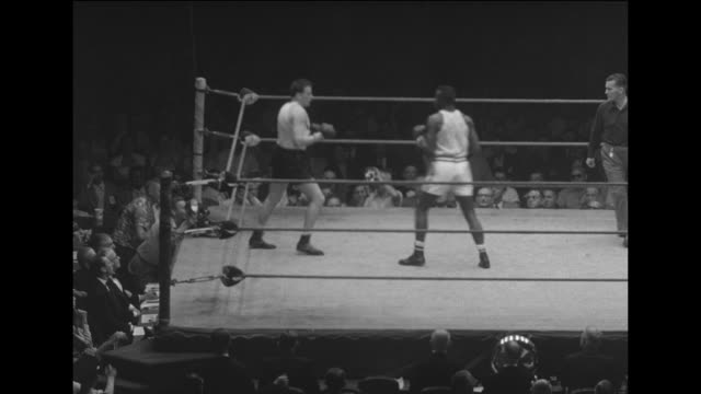 sports fists across the sea / sammy williams fights jacques chandeau in chicago for the middleweight international golden gloves championship / ws... - ボクシングリング点の映像素材/bロール