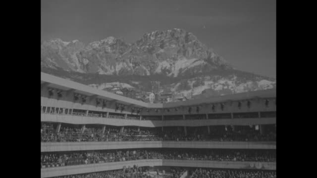 sports grows larger in frame against black background / title the winter olympics superimposed over shot of italian alps / vs high angle of stadio... - 1956 bildbanksvideor och videomaterial från bakom kulisserna