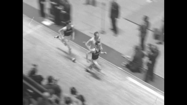 sports / title card k of c track meet superimposed over high shot racing track at madison square garden spectators in foreground stand as racers run... - men's track stock videos and b-roll footage