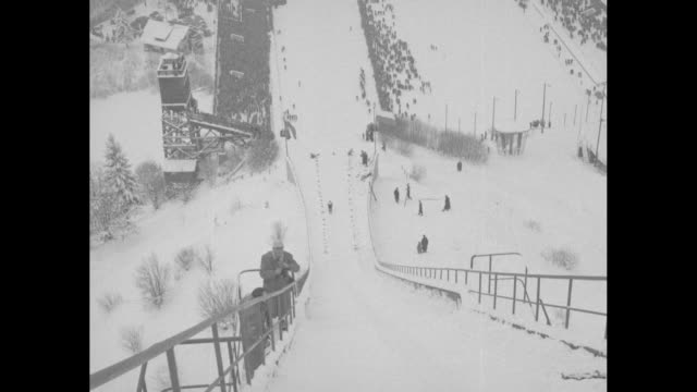"vídeos de stock, filmes e b-roll de ""sports!"" / title: ""international ski jumping!"" superimposed over skier making ski jump, landing on slope during a four hills tournament competition... - contestant"