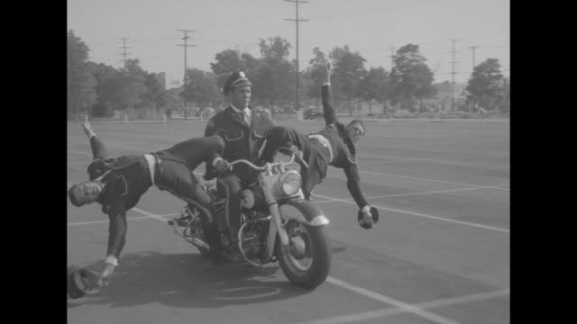 """""""sports!"""" / title: """"men tame wild cycles"""" superimposed over men approaching camera on motorcycles holding up american flags / 2 motorcycles... - stunt person stock videos & royalty-free footage"""
