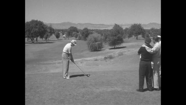 vídeos de stock, filmes e b-roll de sports / title superimposed on us president dwight eisenhower's golf swing golfing with the president / vs ike tees off he and others walking on... - dwight eisenhower