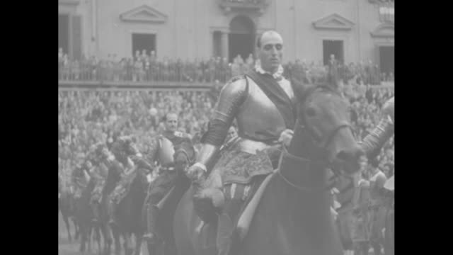 sports / title this is how football began 600 years ago superimposed over armored men in 14th century period costume marching past camera on st... - sports period stock videos & royalty-free footage